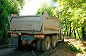 stock photo of dump_truck  - A dump truck unloading gravel for a river side walking path in a small park city park in Oregon - JPG