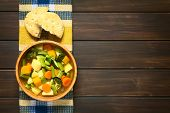 picture of vegetable soup  - Wooden bowl of vegetable soup made of zucchini green bean carrot broccoli potato and pumpkin with a bun on kitchen towel photographed on dark wood with natural light - JPG