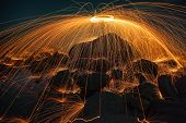 picture of slag  - Showers of hot glowing sparks from spinning steel wool on the rock and beach - JPG
