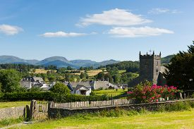 foto of english rose  - Beautiful English country village of Hawkshead Lake District Cumbria UK in summer with blue sky church and pink roses - JPG