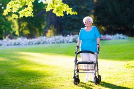 image of handicapped  - Happy senior handicapped lady with a walking disability enjoying a walk in a sunny park pushing her walker or wheel chair aid and support during retirement concept - JPG