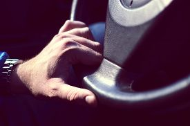 foto of designated driver  - Male driver hands holding steering Wheel and driving - JPG
