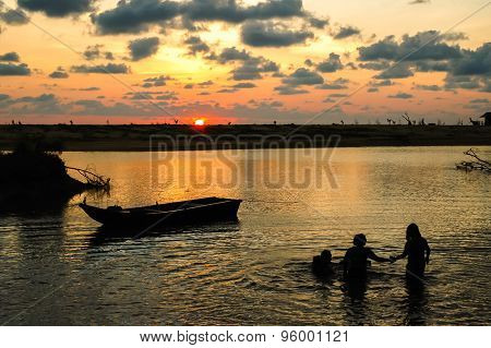 Silhouettes Boat At Beach And Sunset