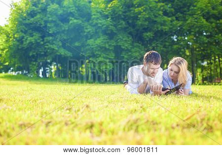 Modern Lifestyle And Ideas: Caucasian Tranquil Couple Lying On Grass Outdoors And Reading Ebook Read