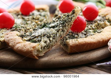 Slices of open pie with spinach and tomato cherry on table close up