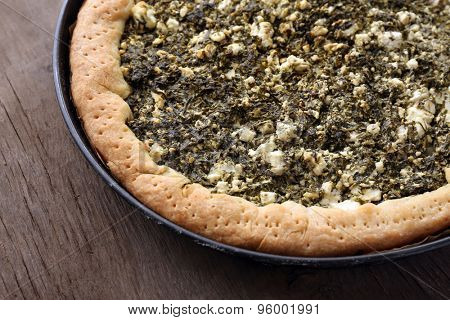 Open pie with spinach on wooden table close up