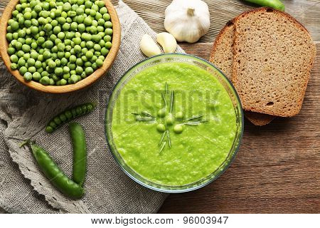 Green pea soup in glass bowl on wooden cutting board with sackcloth, top view