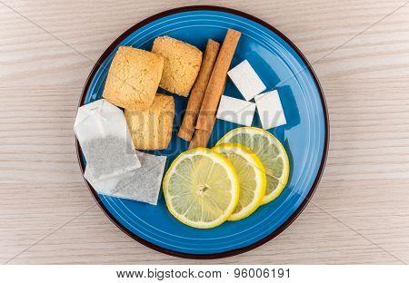 Tea Bags, Sugar, Cinnamon Sticks, Slices Of Lemon And Shortbread