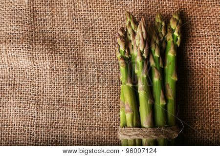 Fresh asparagus on sackcloth background