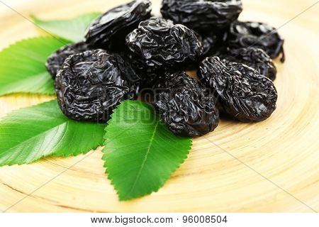 Pile of prunes with leaves on wooden tray, closeup