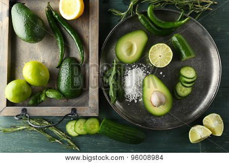 Sliced avocado, cucumber/ pepper and lemon lime on wooden background