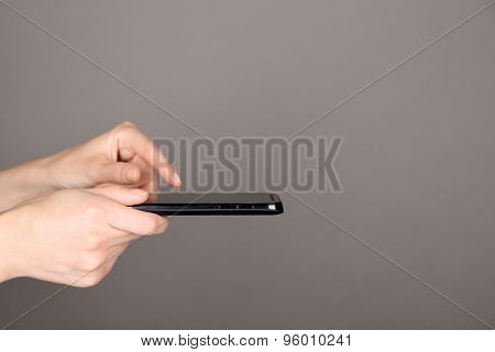 Female hands using mobile phone on gray background