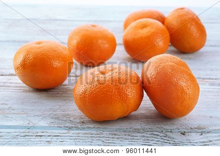 Ripe tangerines on wooden background