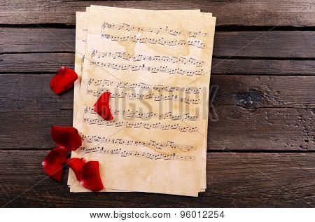 Beautiful rose petals on music sheets on wooden background