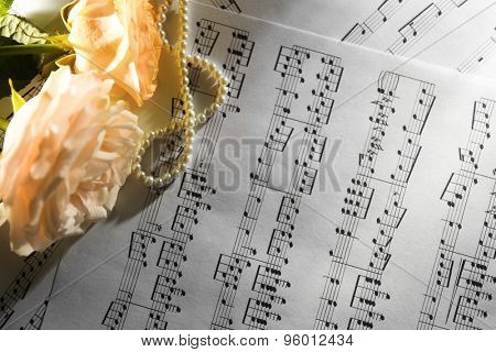 Beautiful roses with pearls on music sheets background