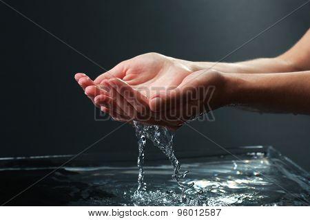 Female hands with water splashing on dark background