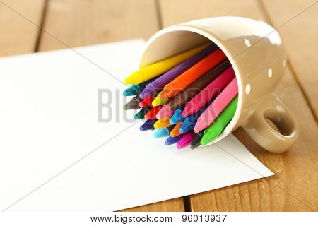 Colorful pastel crayons with sheet of paper on wooden table, closeup