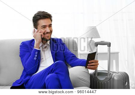 Business man with suitcase sitting on sofa at home