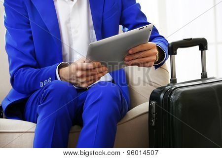 Business man with suitcase and tablet sitting on sofa in hall