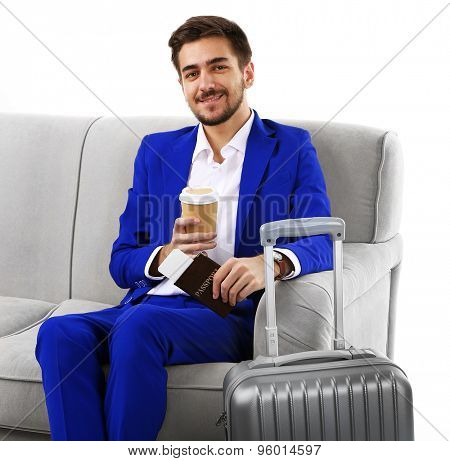 Business man with suitcase sitting on sofa isolated on white