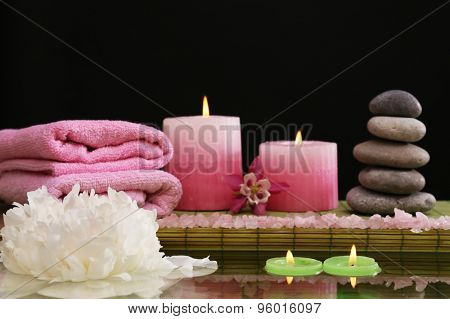 Spa still life with flower and candlelight on black background