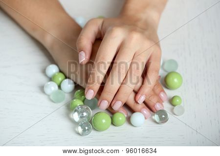 Woman hands with french manicure and glass beads on table close-up