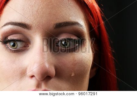 Face of young woman with tear drop close up