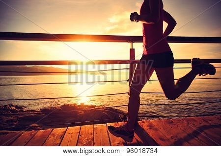 young fitness woman legs running on sunrise seaside trail
