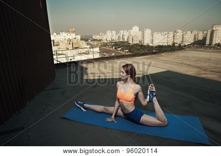 beautiful red haired lady does the splits on roof