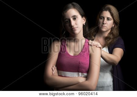 Sad and troubled teenage girl with her mother trying to comfort her isolated on black