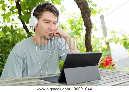 young man with a tablet pc, with headphones, outdoor