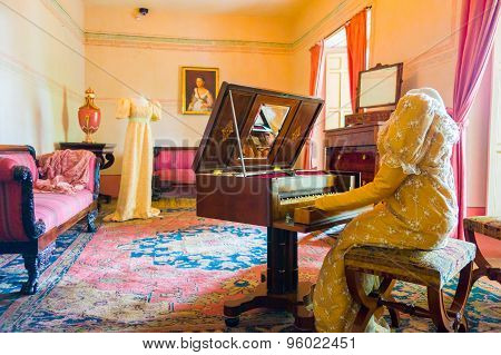 Living room decorated in wooden tables including gold painted details, yellow carpet with a female d