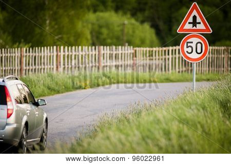 Car on a country road with limited speed and crossroad sign