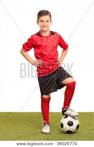 Full length portrait of a junior soccer player stepping over a soccer ball and looking at the camera isolated on white background
