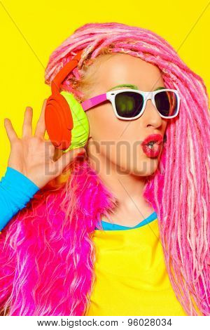 Glamorous modern DJ girl wearing bright clothes, headphones and bright dreadlocks. Disco, party. Bright fashion.