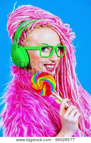 Trendy glamorous girl eating lollipop. Bright style.