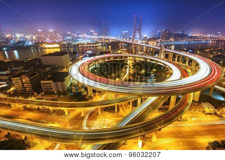 Illuminated skyline and road intersection in shanghai