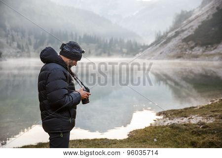 Photographer Holding A Camera, Checking Photos