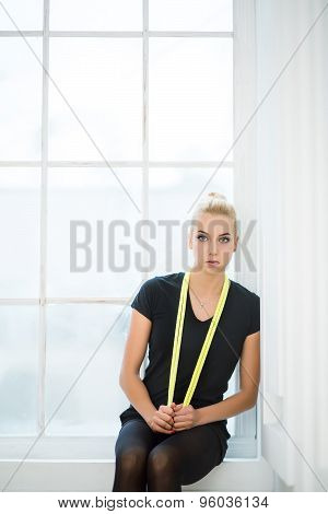 Rhythmic gymnast sitting with yellow rope slung over the neck