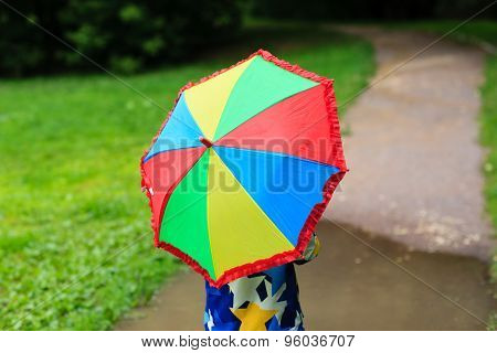 little boy hiding behind colorful umbrella outdoors