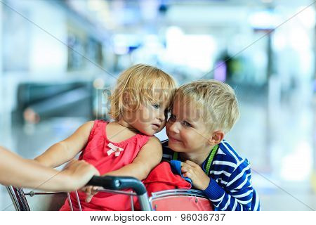 happy kids at airport riding on luggage cart