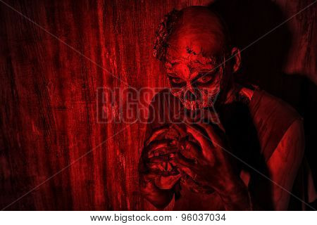 Frightening bloody zombie man in blood-red light. Halloween.