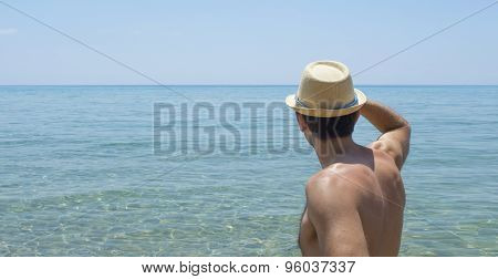 Young Man Looking At The Horizon Wearing Straw Hat