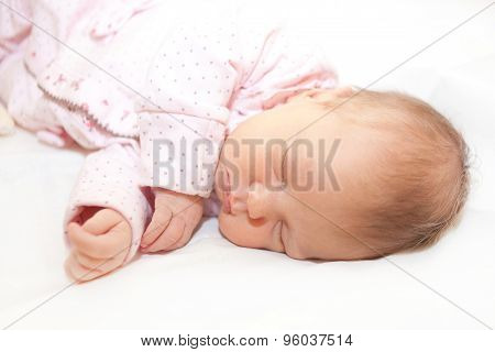 Newborn Baby Is Sleeping On White Bed