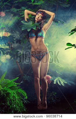 Full length portrit of a beautiful sexy woman in bikini among tropical plants. Beauty, fashion. Spa, healthcare. Tropical vacation.