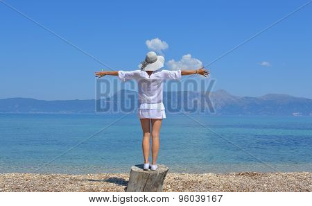 Young Woman Looking At The Mountains Above Sea With Her Arms Wide Open