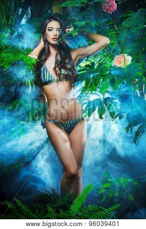 Beautiful sexy woman in bikini among tropical plants. Beauty, fashion. Spa, healthcare. Tropical vacation.