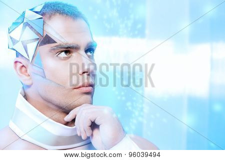 Close-up portrait of a handsome man with futuristic make-up and hairstyle standing on a luminous transparent background.