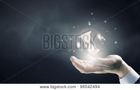 Close up of businessman holding sandglass in hand