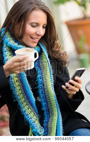 Beautiful woman reading text message holding coffee
